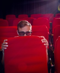 Young man watching a scary 3d film