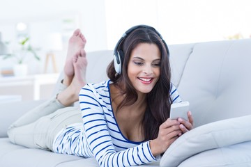 brunette relaxing on the couch and listening music