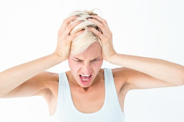 Angry blonde woman screaming and holding her head