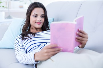 brunette relaxing on the couch and reading a book
