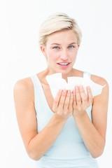 Sick woman holding tissues looking at camera
