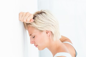 Sad blonde woman with her head on wall