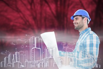 smiling engineer looking away while holding blueprint