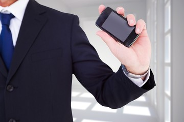 mid section of a businessman typing on his phone