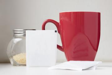 Tea sachet with teabag red teacup and brown sugar