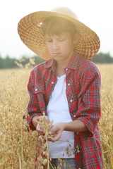 Portrait of teenage farmer boy holding oat seeds with outer