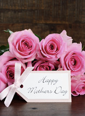 Mothers Day pink roses on rustic dark wood table.