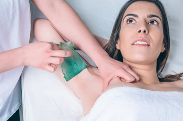 Beautician hands doing depilation in woman armpit with wax strip