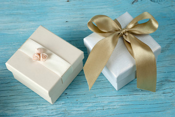Gift boxes with ribbon on old wooden table