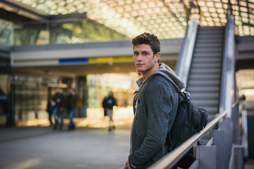Profile shot of handsome young man inside train station