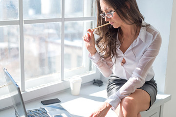 businesswoman sitting next to the window in front laptop