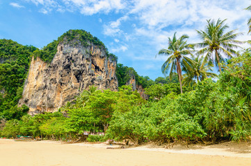 Amazing Railay Beach with mogotes, long tail boat and red kayaks