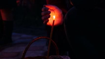 Рука оберегающая пламя свечи на пасхальном куличе.