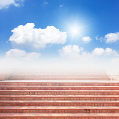 Red brick staircase and blue sky with sun
