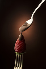 spoon with chocolate,over the strawberry