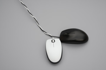 white and black mouses with cables twisted on grey background
