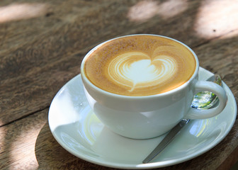 A cup of coffee with heart pattern in a white cup on wooden back