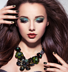 Beautiul  woman with  long brown hairs, turquoise make-up and na