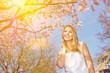 Frau an Tag mit Sonne unter Kirschblüten