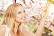 Junge Frau riecht im Flühling an Kirschblüten