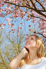 Junge Frau unter Baum mit Kirschblüten