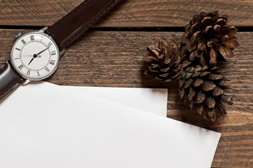 Set of pines watch and paper sheets on wooden table