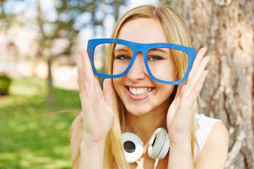 Frau hält Brille aus Holz vor Gesicht