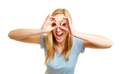 Frau schaut mit Augen durch Finger