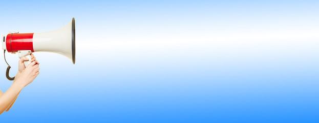 Hand hält Megafon vor Hintergrund in blau