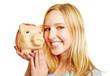 Frau lächelt mit Sparschwein auf der Hand