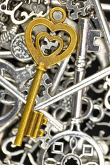 Golden antique key on pile of metallic keys closeup