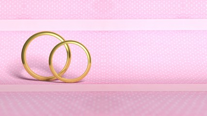 Pair of gold wedding rings, on pink polka dots background
