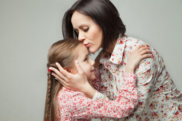 Beautiful and happy young mother kissing her small daughter.