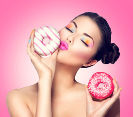 Beauty fashion model girl taking colorful donuts
