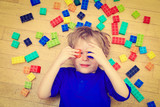 Fototapety child playing with colorful plastic blocks indoor