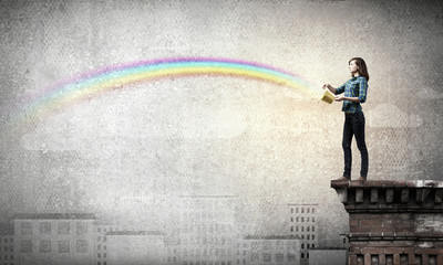 Young man in casual splashing rainbow from bucket