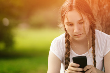 teen girl sitting near tree with mobile phone outdoors