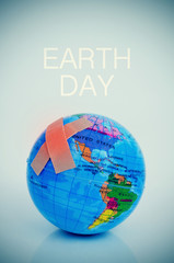 adhesive bandages on a terrestrial globe and the text earth day