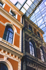 The ancient building is reflected in a modern house of glass