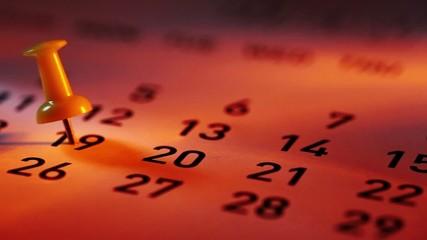 Pan shot of Push pin on a calendar