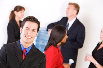 Business: Smiling Businessman with Group Around the Water Cooler