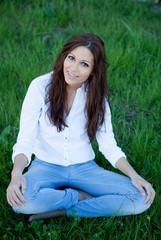 Brunette girl with brackets sitting on the grass