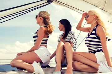 smiling girlfriends sitting on yacht deck