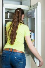Girl standing near fridge