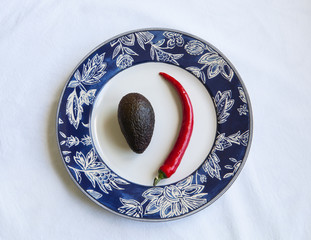 Chile Pepper and avocado on a plate, white background