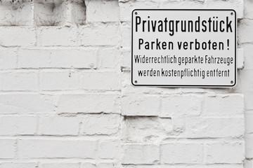 Privatgrundstück Parken verboten - auf alter weisser Ziegelwand