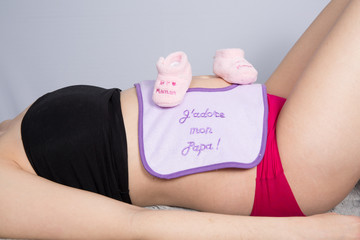 woman holding pink baby booties on her tummy,