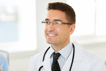 smiling male doctor in white coat and eyeglasses