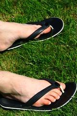 "repos des pieds en tongs dans l""herbe"