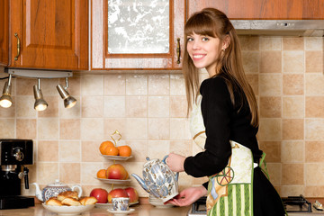 Young woman holding the teapot in her hand